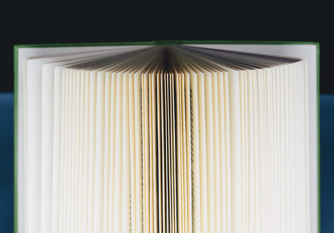 A hard cover printed book, opened and upright. Pages fanned out with graduated yellowing edges, changing to brown and black in the centre.